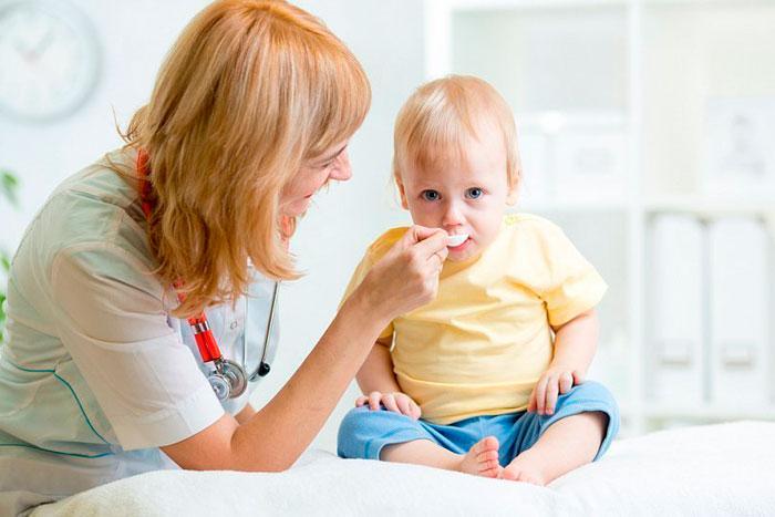 ребенок принимает таблетки с ложечки